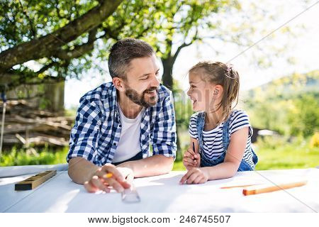 Mature father and a small daughter outside, planning wooden birdhouse or bird feeder. Sketches making. stock photo