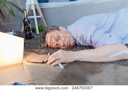 Sign of alcoholism. Inebriate mature man lying on floor and closing eyes stock photo