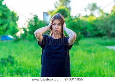 A girl in summer in park black T-shirt. Beautiful asian. He covers his ears with his hands. Emotionally loud noise. Headache. Unwillingness to listen to interlocutor. Something terrible happened. stock photo