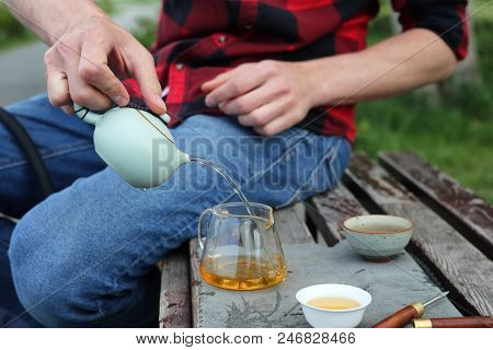 the master gives the Chinese some tea. a teapot with a drop. tea on the street. tea outdoors. ware on a wooden bench on a green background. tea ceremony outdoors. stock photo