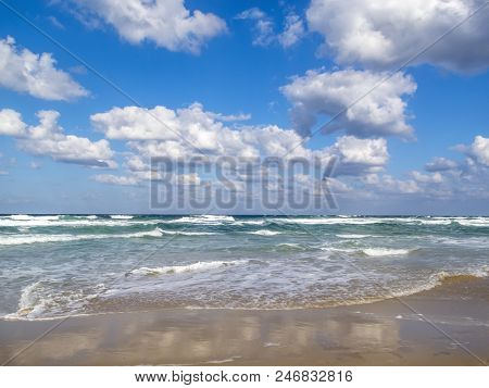 Waves spread on a sandy Bulgarian coastline Black Sea beach, cloud reflections on the sand, beautiful cumulus clouds in the sky, at the seaside resort of Primorsko stock photo