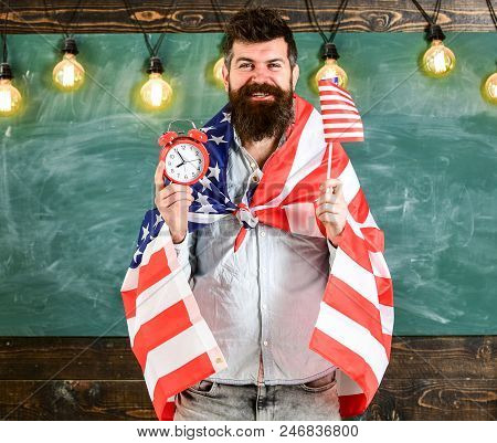 Man with beard on happy face holds flag of USA and clock in classroom, chalkboard on background. American educational system concept. American teacher with american flags holds alarm clock. stock photo