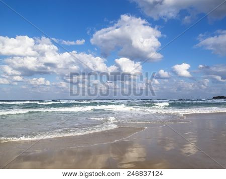 Waves spreading on a sandy Bulgarian coastline Black Sea beach, cloud reflections on the sand, beautiful cumulus clouds in the sky, at the seaside resort of Primorsko stock photo