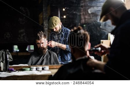Barber with clipper trimming hair on nape of client. Hipster hairstyle concept. Hipster client getting haircut. Barber with hair clipper works on haircut of bearded guy barbershop background. stock photo