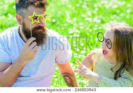 Dad and daughter sits on grass at grassplot, green background. Family spend leisure outdoors. Child and father posing with eyeglases photo booth attribute while speaking. Communication concept. stock photo