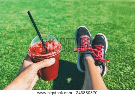 Girl drinking red beet or fruit smoothie plastic cup during fitness workout. Healthy detox juice woman holding drink shower running shoes in food selfie photo. Sport active lifestyle stock photo