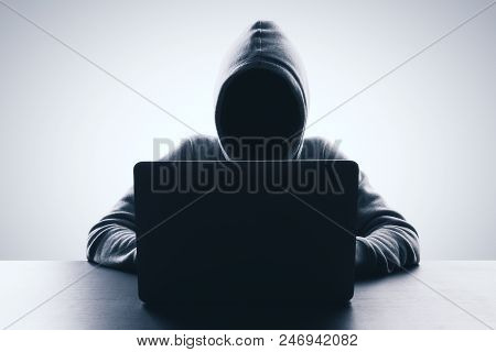 Man with hood using laptop on gray background. Hacker and web attack concept. Copy space stock photo