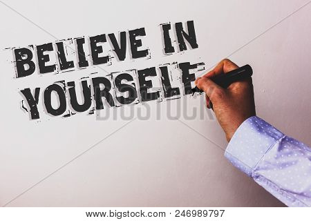 Handwriting text Believe In Yourself. Concept meaning Determination Positivity Courage Trust Faith Belief Advisors hand holding black marker whiteboard written black color words stock photo