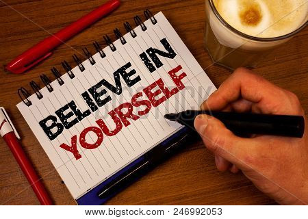 Word writing text Believe In Yourself. Business concept for Determination Positivity Courage Trust Faith Belief Hand grasp black marker wooden desk red pen notepad expos texts coffee stock photo
