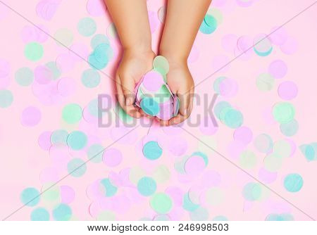 Colorful confetti background with child's hands holding confetti. Festival and bright. Top view, flat lay. Copy space for your text stock photo