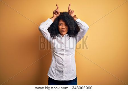 Young beautiful african american elegant woman with afro hair standing over yellow background doing funny gesture with finger over head as bull horns stock photo
