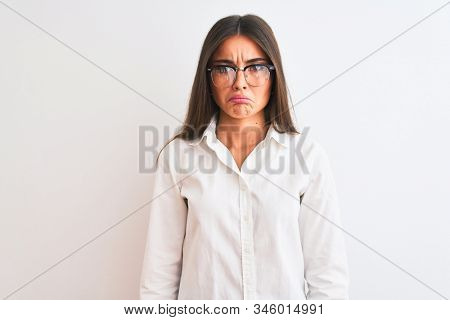 Young beautiful businesswoman wearing glasses standing over isolated white background depressed and worry for distress, crying angry and afraid. Sad expression. stock photo