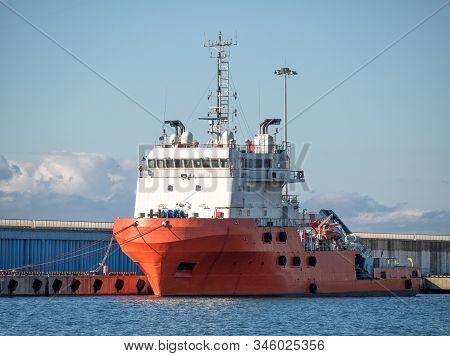 Platform supply vessel anchored in sea port at sunny day. Front view of offshore support vessel stock photo