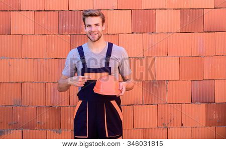 General maintenance repair worker fix maintain building. Inspect diagnose problems figure out way correct. Man build house. Inspecting building. Worker brick wall background. Building construction stock photo