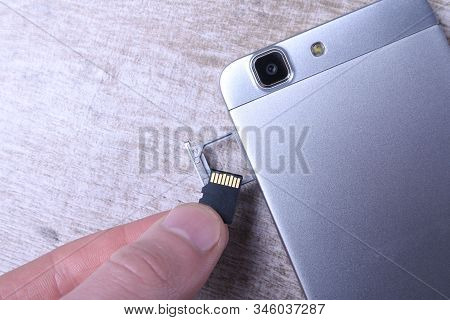 Flash memory data storage concept : A tray with a micro SD card on white background. A memory card is used for storing digital information in portable electronic devices e.g mobile phone, tablets stock photo