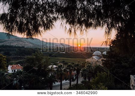 Architecture and nature of Turkey.Ruins of old city.Archaeological excavations.Old red brick arch.City view.Background for travel.Trees and mountains.Sunset on background of mountains.Selcuk, Turkey. stock photo