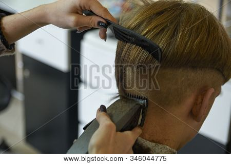 Hairdressing services. A man cuts hair at a hairdresser-stylist in a barbershop. scissors comb, clipper close-up.Barber at work. Close up cutting on hair. stock photo