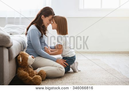 Family concept. Adorable little girl cuddling with her pregnant mother at home, copy space stock photo