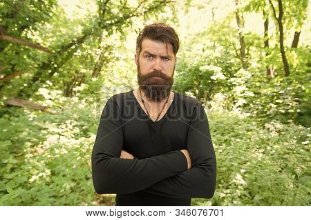 His brutal style. Brutal hipster wearing casual style outdoor. Bearded man with brutal look keeping arms crossed. Brutal caucasian guy with long beard and mustache on summer nature. stock photo