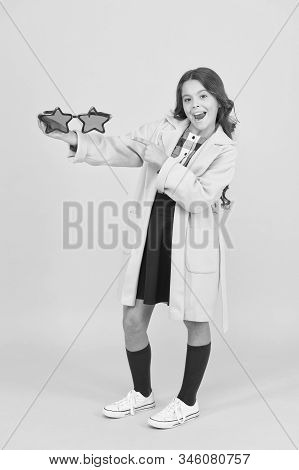 Look at life through star-shaped glasses. Happy girl point finger at party glasses. Little child with funny glasses. School party. Holiday celebration. Get right pair of glasses for special occasion. stock photo