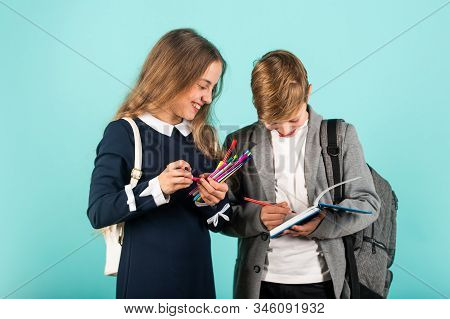 Before examination. Small children prepare for examination. Little girl and boy hold examination paper. Taking writing test. Examination in English. School and education stock photo