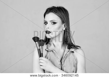 Looking good and feeling confident. Makeup dark lips. Attractive woman applying makeup brush. Professional makeup supplies. Makeup artist concept. Emphasize femininity. Girl apply powder eye shadows stock photo