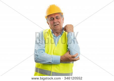 Old male construction worker touching elbow with hurting expression isolated on white studio background stock photo