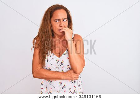 Middle age mature woman standing over white isolated background looking stressed and nervous with hands on mouth biting nails. Anxiety problem. stock photo