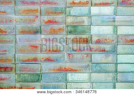 Abstract background of shiny glass bricks. Mosaic texture, abstract geometric pattern. A colourful glass blocks wall backdrop. Structured surface. Architecture, interior. stock photo