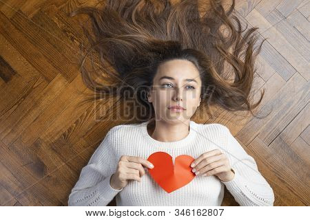 Unhappy young woman with broken heart tearing up a red paper heart. Lying on the ground, unhappy and sad. Loneliness and divorce stock photo