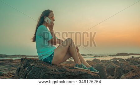 Relaxed woman sitting on stone and speaking on smartphone on shore. Side view of pleasant woman spending time enjoying vacation and talking on mobile phone on stony shore stock photo