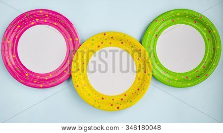 Bright yellow, green and pink paper plates on a blue background. Paper decoration with a ribbon on a blue background. The concept of holiday dishes, dishes for a picnic. Eco dishes. Selective focus. stock photo