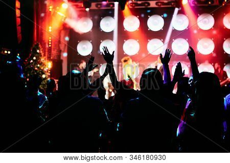 Crowd at a music concert, audience raising hands up in front of bright stage lights. stock photo