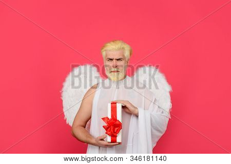 Valentines day angel. Cupid. Serious man in angel costume. February 14. Cupid with gift. Love concept. Cupid with gift box. Valentine angel. Cupid angel with present box. Happy Valentines Day. Amour stock photo