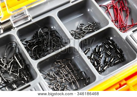 Opened tackle box with fishing hooks and accessories. Fishing hooks in box sections. Case for tackle elements. Fishing accessories background close-up. stock photo