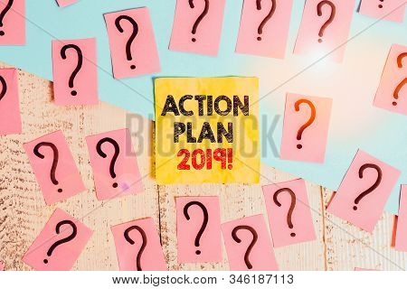 Text sign showing Action Plan 2019. Conceptual photo proposed strategy or course of actions for current year Scribbled and crumbling papers with thick cardboard above wooden table. stock photo