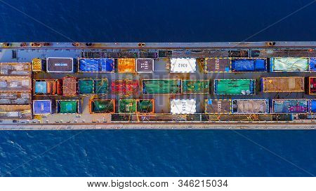 Cargo Ship Loaded With Colourful Containers And Large Crates Cruising At Sea, Top Down Aerial View.