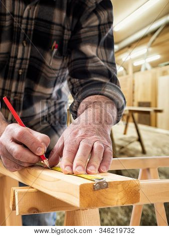 Close-up. Carpenter with pencil and carpenter's square draw the cutting line on a wooden board. Construction industry, carpentry workshop. stock photo