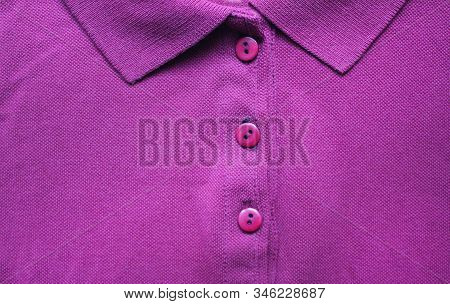 Violet colorful polo shirt with buttoned collar neck. Stylish modern clothing, dark purple colour t-shirt close up view, simple cotton shirt design stock photo