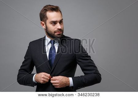 Handsome young business man in classic black suit shirt tie posing isolated on grey background. Achievement career wealth business concept. Mock up copy space. Fasten button on jacket, looking aside. stock photo