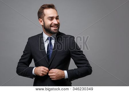 Cheerful young business man in classic black suit shirt tie posing isolated on grey background. Achievement career wealth business concept. Mock up copy space. Fasten button on jacket, looking aside. stock photo