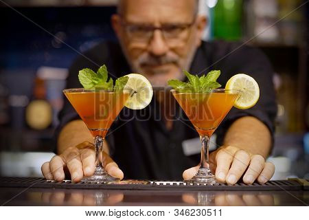 Elderly bartender gives two red cocktail. Fresh cocktail with grapefruit. Alcoholic, non-alcoholic drink-beverage at the bar counter in the night club. Two grapefruit cocktail. stock photo