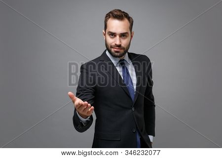 Confident young business man in classic black suit shirt tie posing isolated on grey background. Achievement career wealth business concept. Mock up copy space. Pointing outstretched hand on camera. stock photo