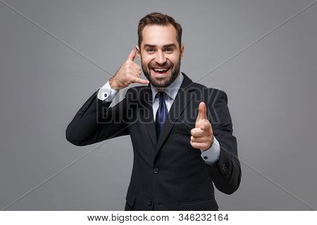 Young business man in suit shirt tie posing isolated on grey background. Achievement career wealth business concept. Mock up copy space. Doing phone gesture like says call me back, point index finger. stock photo
