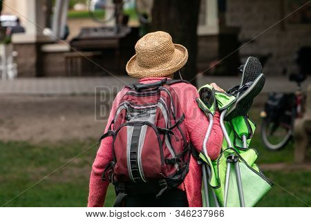 Rear View Of Unrecognizable Person Wearing Backpack And Sun Hat While Holding Green Hiking Equipment