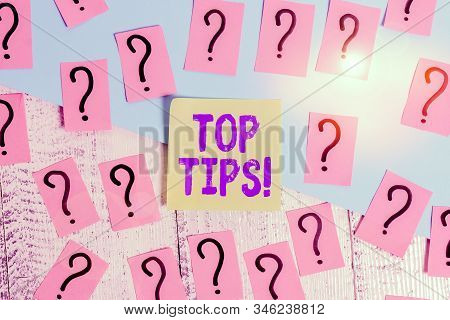 Conceptual hand writing showing Top Tips. Business photo text small but particularly useful piece of practical advice Crumbling papers with thick cardboard on the wooden table. stock photo