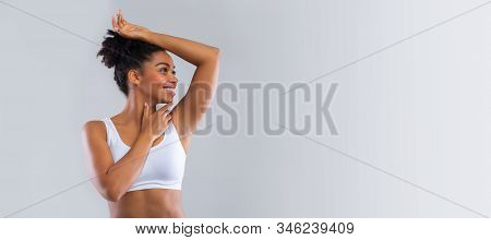 Cheerful black woman smelling her fresh armpit over grey background, putting hand up, panorama with copy space, advertisement for under arm epilation stock photo