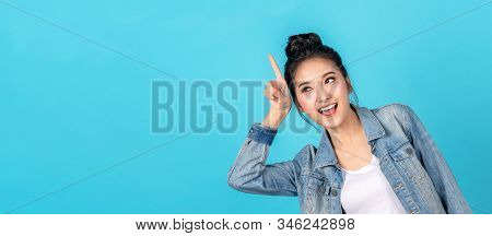Banner of Happy asian woman standing pointing hands to copyspace on blue background. Cute asia girl smiling wearing casual jeans shirt and finger pointing to aside for present promotions. stock photo