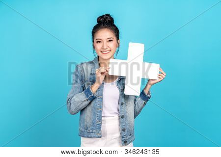 Happy asian woman standing and holding plus or add sign on blue background. Cute asia girl smiling wearing casual jeans shirt and showing join sign for increse, upgrade and more benefit concept stock photo