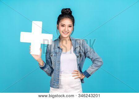 Happy asian woman smiling hand on hip and showing plus or add sign on blue background. Cute asia girl smiling wearing casual jeans shirt and showing join sign for increse and more benefit concept stock photo